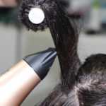An up-close image of someone blow drying hair.